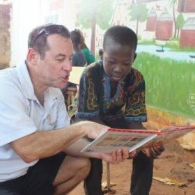 An older volunteer reads to a child as part of his childcare volunteer work overseas